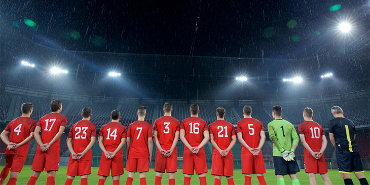 Line of football players from behind showing their shirt numbers