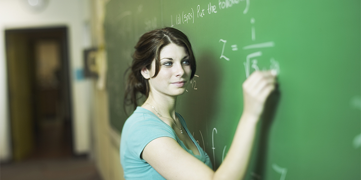A young woman writing a mathematical equation on a chalkboard
