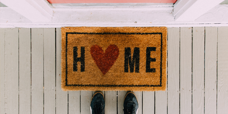 A pair of feet near a doormat with the word Home written on it, the letter o is a heart
