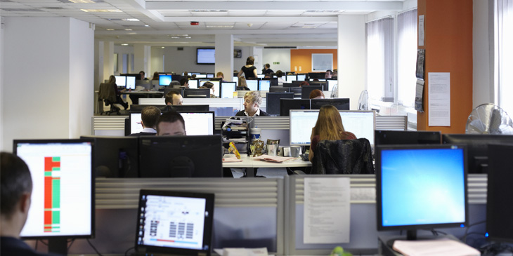 View of an office setting where people are sat in-front of their computer stations
