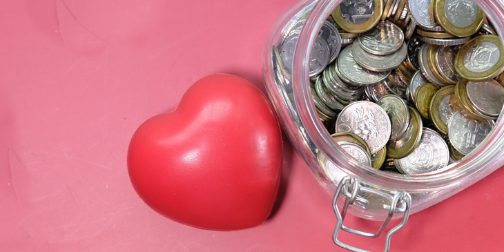 A love heart next to a jar filled with coins