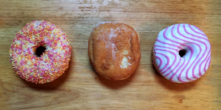 Three different types of doughnuts placed on a wooden surface