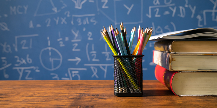 A pile of book and a collection of pencils in a pencil cup on a table, with a blackboard filled with mathematics in the background