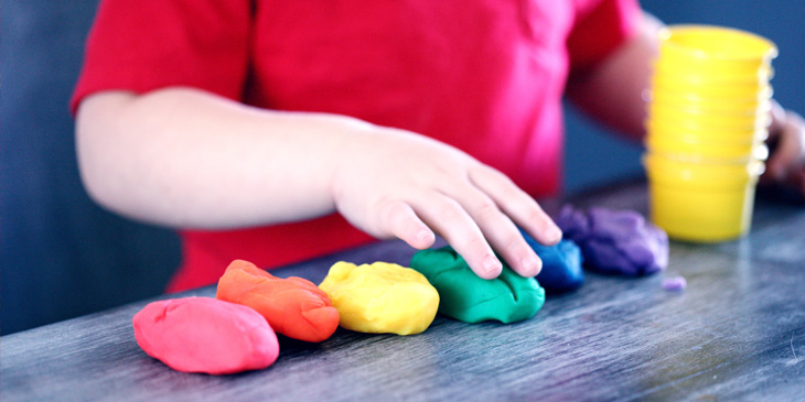 A child playing with different coloured piles of Play-Doh