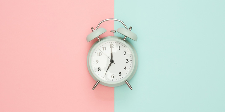 An old fashioned alarm clock on a half pink half blue background