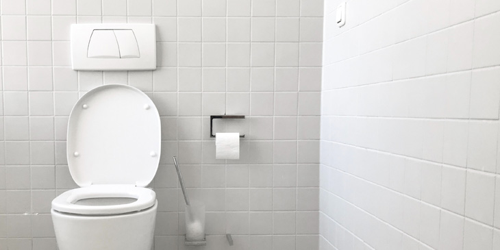 A toilet with push buttons of two different sizes, in a tiled room